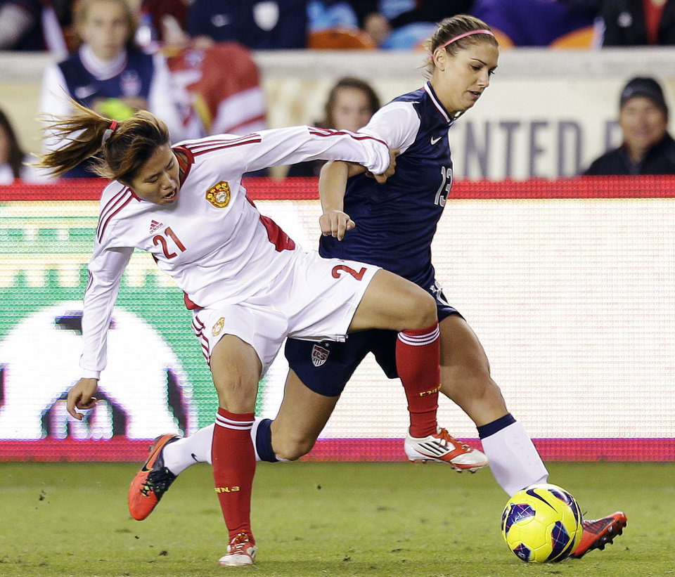 China's Wang Lisi and United States' Alex Morgan (13) go after the ball during the first half of an exhibition soccer match, Wednesday, Dec. 12, 2012, in Houston. (AP Photo/David J. Phillip)