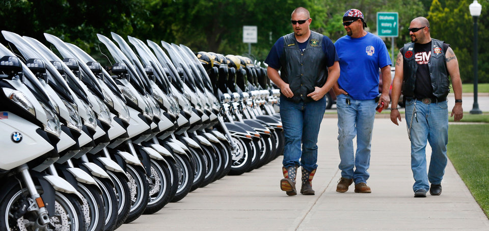 Photo -  Bryan Goostree, Kenneth Perrryman and Travis Gonzales walk past a line of police motorcycles parked on a sidewalk at the safety event.    JIM BECKEL -  THE OKLAHOMAN