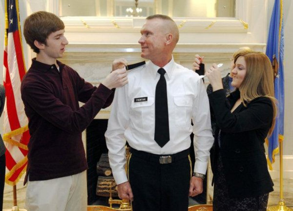 Photo - Brig. Gen. Walter Fountain has his stars pinned onto his shirt by his children, Eric and Lauren, during a pinning ceremony at the state Capitol.