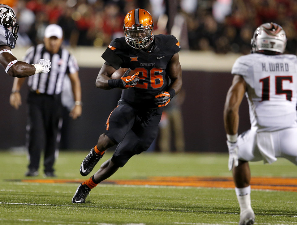 Photo - Oklahoma State's Desmond Roland (26) rushes during a college football game between the Oklahoma State Cowboys (OSU) and the Texas Tech Red Raiders at Boone Pickens Stadium in Stillwater, Okla., Thursday, Sept. 25, 2014. Photo by Bryan Terry, The Oklahoman