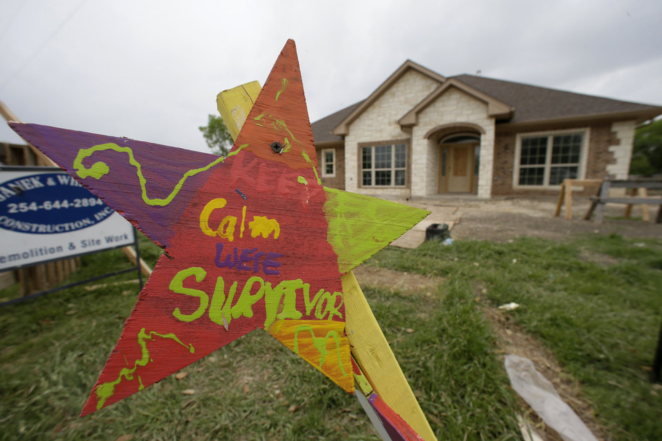 Photo - A sign in the shape of the star has a hand painted message that reads, Keep Calm We're Survivors, in front of a newly constructed home where a nearby fertilizer plant exploded one year ago today, Thursday, April 17, 2014, in West, Texas.Today marks the one year anniversary of the explosion at a fertilizer plant that killed fifteen people, including 12 volunteer firefighters and others responding to the fire, and more than 200 were injured. (AP Photo/Tony Gutierrez)