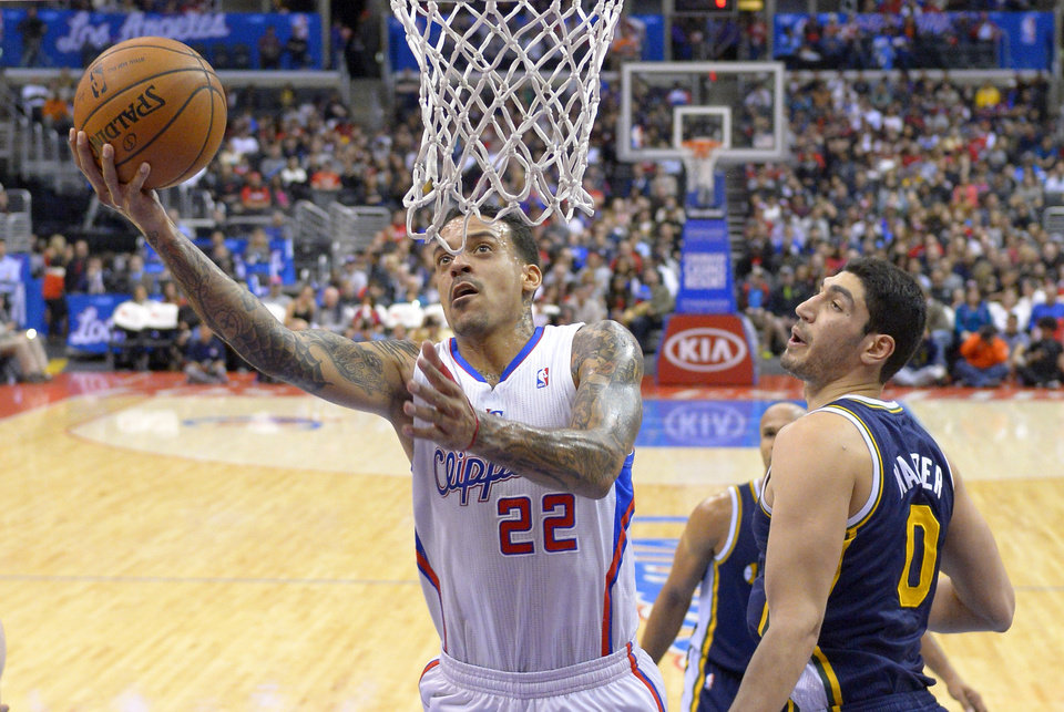 Photo - Los Angeles Clippers forward Matt Barnes, left, puts up a shot as Utah Jazz center Enes Kanter defends during the first half of an NBA basketball game, Saturday, Feb. 1, 2014, in Los Angeles. (AP Photo/Mark J. Terrill)