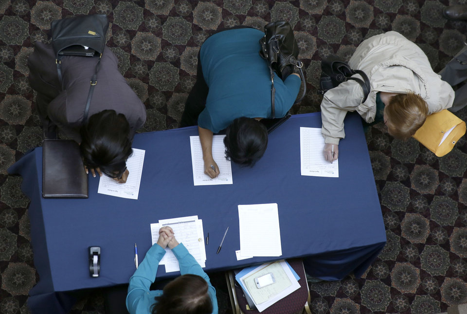 Photo - FILE - In this Jan. 22, 2014, file photo, job seekers sign in before meeting prospective employers during a career fair at a hotel in Dallas. The U.S. economy finally regained the jobs lost during the Great Recession, but the comeback is far from complete. (AP Photo/LM Otero)