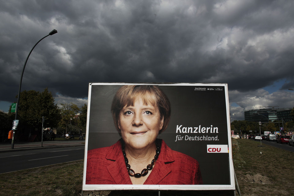 Photo - An election campaign poster of German Chancellor Angela Merkel stands in the sun while  dark clouds come in  on a street in central Berlin, Tuesday, Sept. 17, 2013. Germany faces general elections on Sept. 22, 2013 where Chancellor and Christian Democratic Union (CDU) party chairwoman Angela Merkel will run for her third term .  (Words read (Chancellor for Germany. AP Photo/Markus Schreiber)