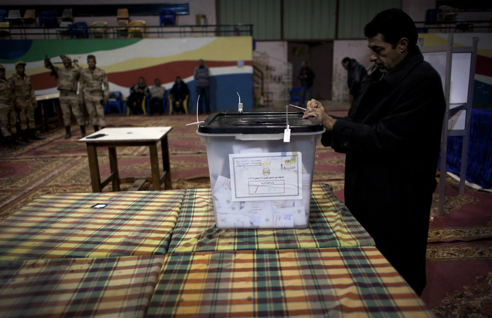 Photo - An Egyptian election worker controls a ballot box ahead of the counting process at the end of the second round of a referendum on a disputed constitution drafted by Islamist supporters of president Mohammed Morsi at a polling station in Giza, Egypt, Saturday, Dec. 22, 2012. Egypt's Islamist-backed constitution headed toward likely approval in a final round of voting on Saturday, but the deep divisions it has opened up threaten to fuel continued turmoil. (AP Photo/Nasser Nasser)