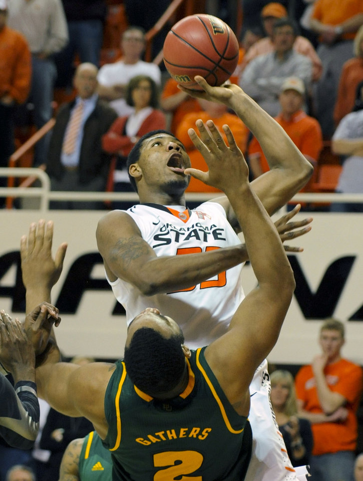 Oklahoma State guard Marcus Smart, top, is fouled by Baylor forward Rico Gathers (2) during the second half of an NCAA college basketball game in Stillwater, Okla., Wednesday, Feb. 6, 2013. Smart scored 14 points in the Oklahoma State 69-67 overtime win over Baylor. (AP Photo/Brody Schmidt)
