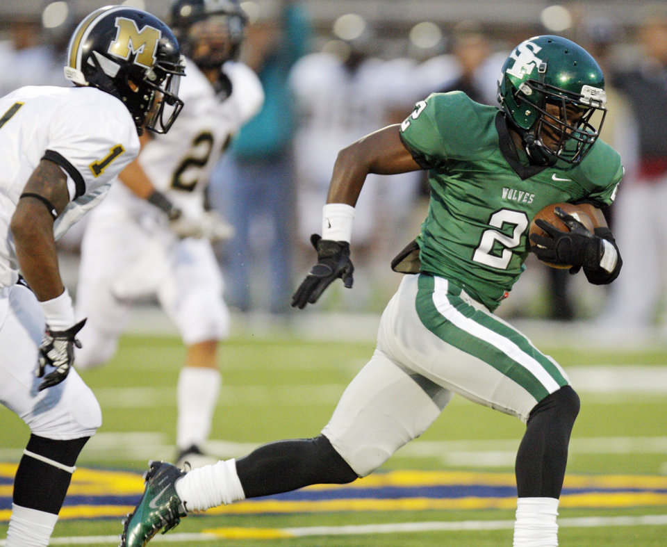 Photo - Trevan Smith (2) of Edmond Santa Fe tries to break away from Ricky Reeves (1) of Midwest City during a high school football game between Midwest City and Edmond Santa Fe at Wantland Stadium in Edmond, Okla., Thursday, Sept. 15, 2011. Photo by Nate Billings, The Oklahoman