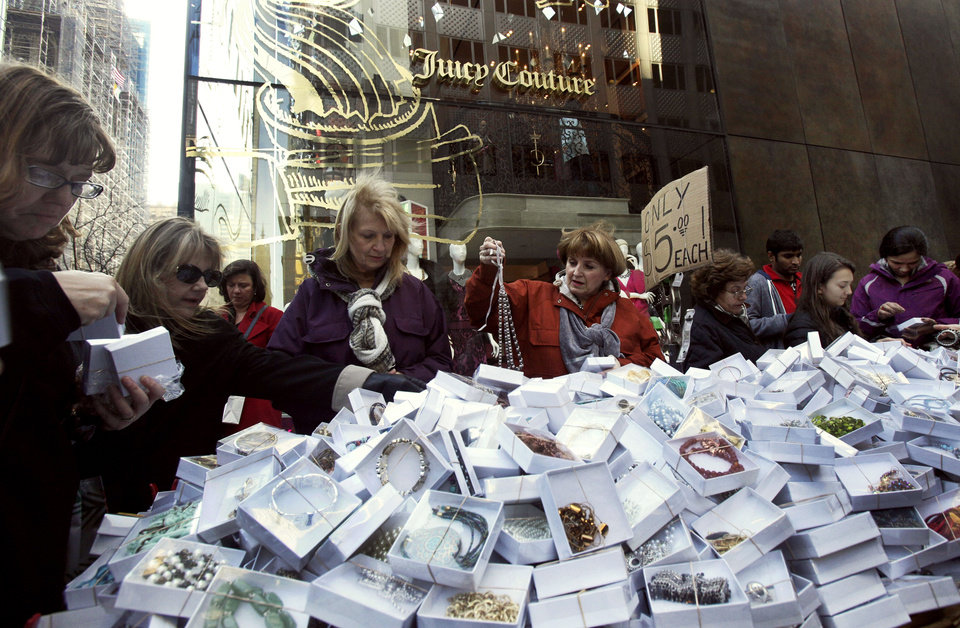 Photo -   Shoppers on New York's Fifth Ave. patronize a street vendor featuring $5 jewelry, Friday, Nov. 23, 2012. Black Friday, the day when retailers traditionally turn a profit for the year, got a jump start this year as many stores opened just as families were finishing up Thanksgiving dinner. (AP Photo/Richard Drew)
