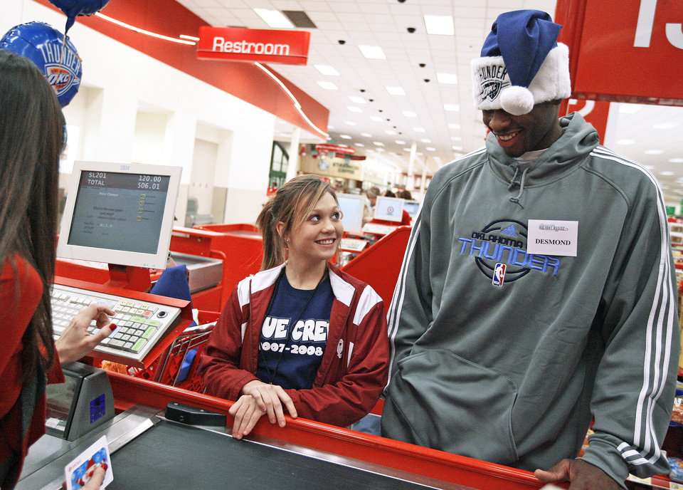 Photo - Desmond Mason goes through the checkout aisle with Annalisa Nolen. Photo BY BRYAN TERRY, THE OKLAHOMAN