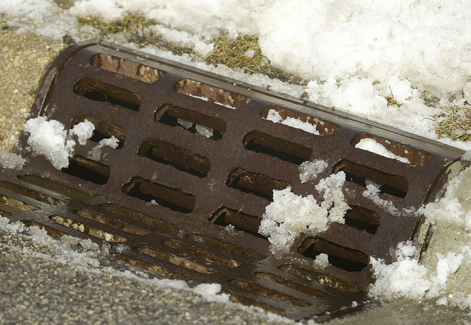 Photo - Snow melts on a storm drain after it was cleared by a public works crew in Crystal Lake, Ill. Wednesday, Feb 18, 2014. Weeks of subfreezing weather are giving way, at least briefly, to temperatures in the 50s, putting cities on guard for flooding, roof collapses and clogged storm drains. (AP Photo/Northwest Herald, H. Rick Bamman)  MANDATORY CREDIT