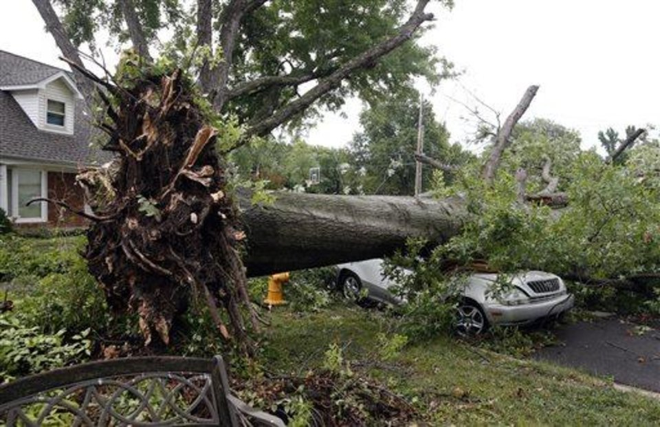 Photo - A car is crushed by an uprooted tree after strong winds hit the area Wednesday, July 24. 2013, in Tulsa, Okla.  Powerful thunderstorms swept through parts of Oklahoma late Tuesday and early Wednesday, knocking out power to tens of thousands of homes and businesses and setting off fires caused by lightning strikes. (AP Photo/Tulsa World,  Tom Gilbert)