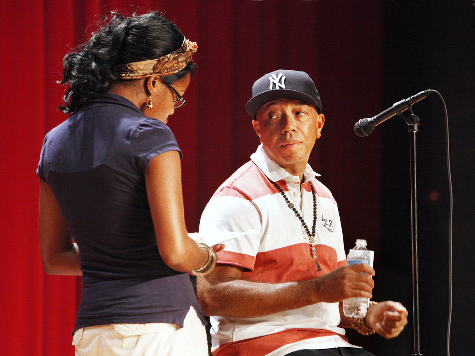 Photo - Russell Simmons, co-founder of the hip-hop label Def Jam and creator of the clothing fashion line Phat Farm, listens to a question from John Marshall High School senior Brianna Herron, 18. Simmons spoke at the northwest Oklahoma City school Wednesday afternoon before speaking to business students at the University of Central Oklahoma, which paid for his visit to Oklahoma. Photo by Paul B. Southerland, The Oklahoman  PAUL B. SOUTHERLAND - THE OKLAHOMAN