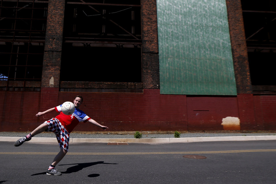 Photo - Jason Burke, 35, left, of Ridgewood, N.J., plays soccer near a warehouse adjacent to Red Bull Arena before the start of an international soccer friendly between Turkey and the United States, Sunday, June 1, 2014, in Harrison, N.J. (AP Photo/Julio Cortez)
