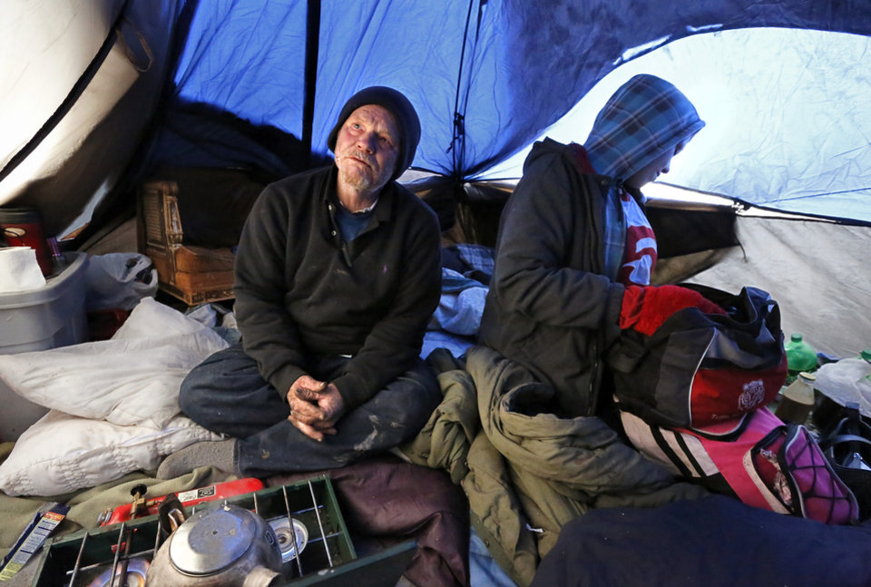 Photo - Jackson Poadger, 53, his dog and three other adults were huddled inside his tent at a homeless encampment hidden by trees near MainStreet and Villa. In preparation for this week's winter storms,  homeless shelters and organizations are ramping up efforts to house people during the coldest days the state has seen in several years. This includes actively going out to documented homeless camps and trying to convince people to accept a ride to an indoor shelter in Oklahoma City, but not everyone agrees to abandon their camps, some out of a fear that their material possessions will be stolen while they're gone.  Jonathon Roberts, with Be the Change, an Oklahoma City based non-profit that provides assistance to the homeless, gave Poadger and his friends extra blankets when he  checked on a number of encampments west of the downtown area Thursday afternoon, Dec. 5, 2013. Photo by Jim Beckel, The Oklahoman