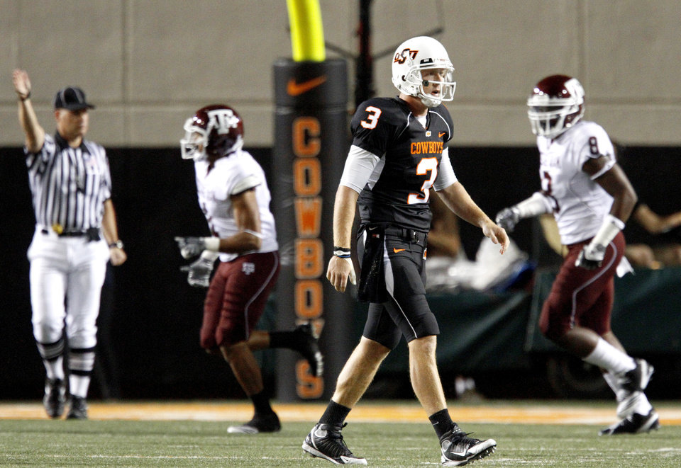 Photo - OSU's Brandon Weeden walks off the field after throwing an interception during the college football game between Texas A&M University and Oklahoma State University (OSU) at Boone Pickens Stadium in Stillwater, Okla., Thursday, Sept. 30, 2010. Photo by Bryan Terry, The Oklahoman