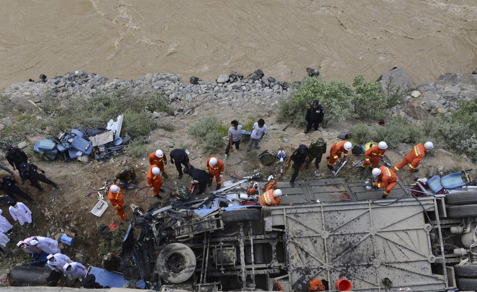 Photo - In this photo released by China's Xinhua News Agency, rescuers work around an overturned tour bus after it fell off a 10-meter (30-foot) cliff in Nyemo County, southwest China's mountainous region of Tibet Saturday, Aug. 9, 2014. Xinhua reported the bus carrying about 40 people careened after it crashed in a pileup involving a sports utility vehicle and a pickup truck on a state road. Casualty details were not immediately known. (AP Photo/Xinhua, Chogo) NO SALES