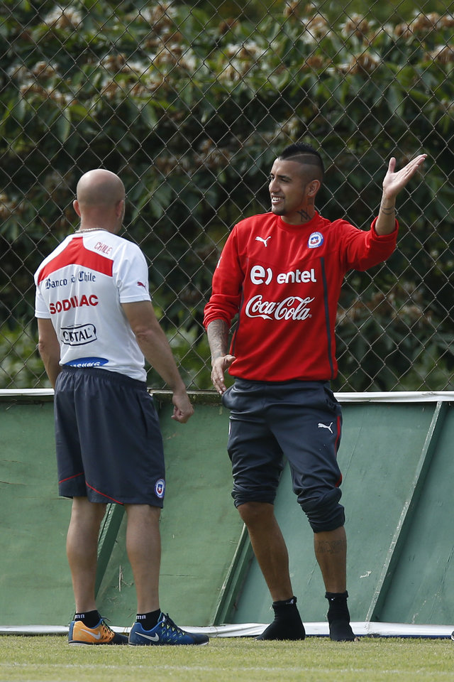 Photo - Chile's Arturo Vidal, right, talks with head coach Jorge Sampaoli during a training session at Toca da Raposa 2 center in Belo Horizonte, Brazil, Thursday, June 19, 2014.  Chile plays in group B of the 2014 soccer World Cup. (AP Photo/Victor R. Caivano)