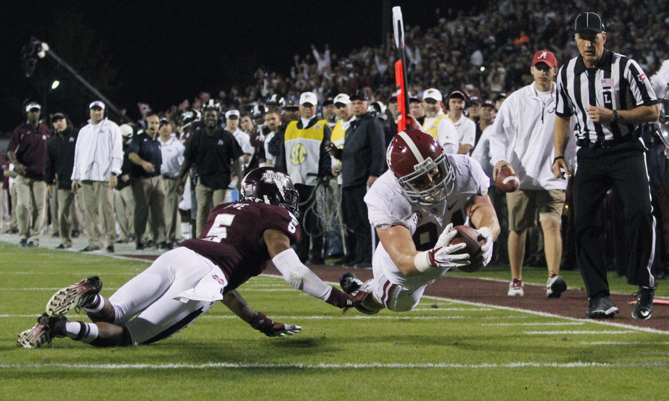 Photo - Alabama tight end Brian Vogler (84) dives into the end zone past Mississippi State defensive back Jamerson Love (5) for an 18-yard touchdown reception during the second quarter of an NCAA college football game, Saturday, Nov. 16, 2013, in Starkville, Miss. (AP Photo/Butch Dill)