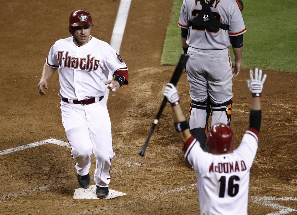 Photo -   Arizona Diamondbacks' Miguel Montero scores as teammate John McDonald greets him at the plate against the San Francisco Giants during the sixth inning of a baseball game, Friday, Sept. 14, 2012,in Phoenix. (AP Photo/Matt York)