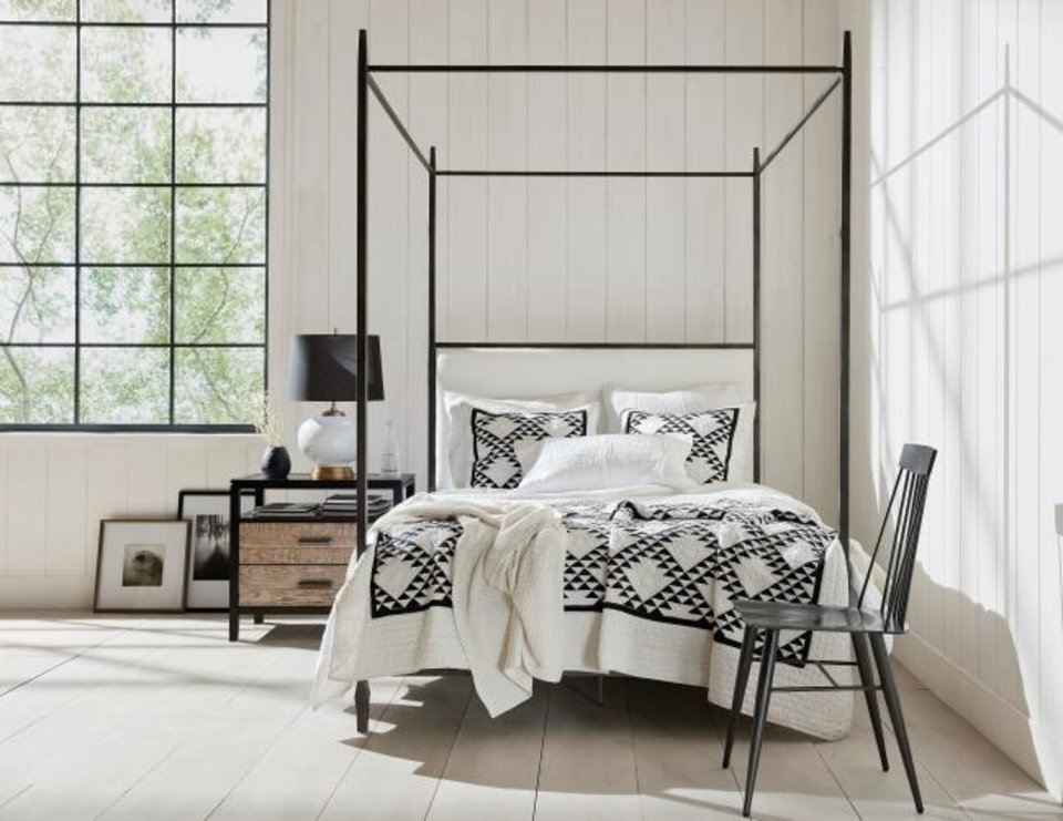 "Photo -  The black-and-white color scheme gives this bedroom an upscale country look, Ethan Allen designer Joanne LaFauci says. ""The patterned quilt and metal bed say country and rustic, but the crisp colors give it a modern edge."" [PROVIDED/ETHAN ALLEN]"