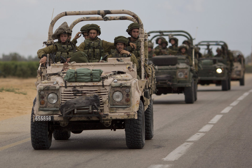 Photo - Israeli soldiers ride on a military vehicle near the Israel-Gaza Border, Thursday, July 17, 2014. Israel and Hamas have begun observing a five-hour humanitarian cease-fire, as fighting extended into a 10th day. The two sides agreed to the pause following a request by the United Nations so that supplies could be delivered to Gaza.(AP Photo/Ariel Schalit)