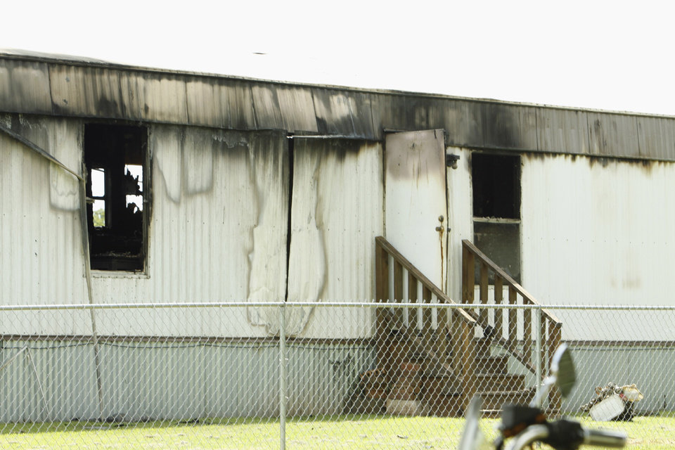 Photo - McClain county detectives found three people dead on July 23 in this house fire  in Dibble.  Photo by Steve Sisney, The Oklahoman