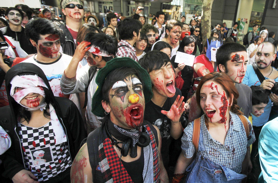 Photo - People dressed as zombies participate in the Zombiewalk Chile 2011: Return of the Dead Heroes march in Santiago, Chile, Saturday Oct. 15, 2011.  Participants dress in a zombie-like version of their favorite childhood heroes as a tribute to their child within that dies when they become adults. (AP Photo/Luis Hidalgo)