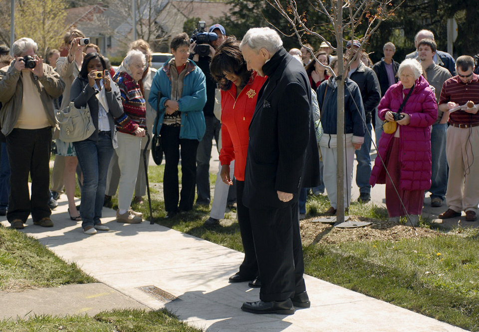 Photo - FILE - In this April 22, 2009 file photo, film critic Roger Ebert and his wife, Chaz, look at a plaque dedicated to Ebert's life and achievements in front of his childhood home in Urbana, Ill. Through his television shows, movies reviews and essays, Ebert belonged to the world beyond nearby Urbana. But if you read the Chicago Sun-Times movie critic closely, you knew a piece of him stayed behind in the college town where he grew up.  The connection between Ebert and the town _ and the University of Illinois, his alma mater _ was strong and permanent. The Pulitzer Prize-winning critic died April 4, 2013, at age 70 after a long battle with cancer. This year's Ebertfest run April 17-21 in nearby Champaign, Ill.  (AP Photo/The News-Gazette, Heather Coit, File)  MANDATORY CREDIT