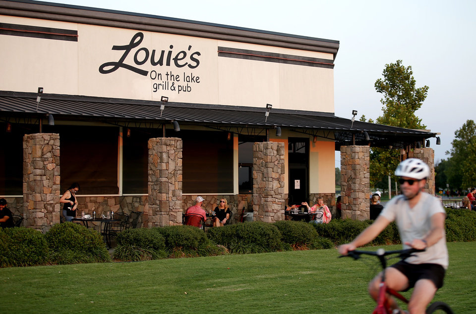 Photo -  People eat outside at Louie's Grill & Bar at Lake Hefner in Oklahoma City. The coronavirus pandemic has impacted various types of retail activities. [Sarah Phipps/The Oklahoman]