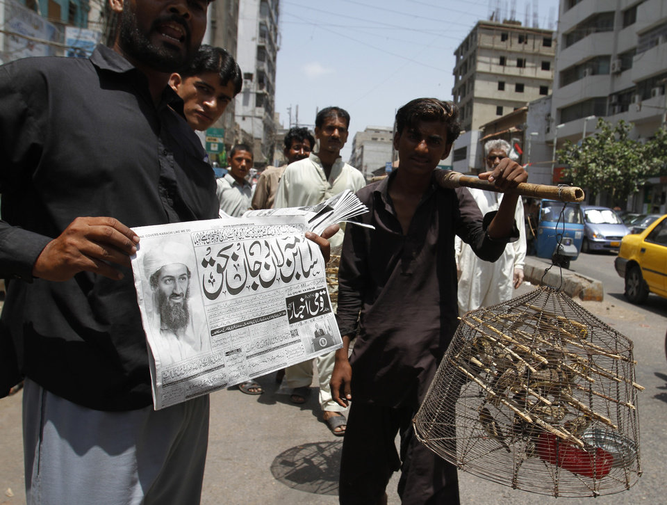 Photo - A man shows a newspaper reporting the killing of Al-Qaida leader Osama bin Laden in Pakistan, in Karachi, Pakistan Monday, May 2, 2011. Osama bin Laden, the glowering mastermind behind the Sept. 11, 2001, terror attacks that killed thousands of people, was slain in his luxury hideout in Pakistan early Monday in a firefight with U.S. forces, ending a manhunt that spanned a frustrating decade. Headline reads: