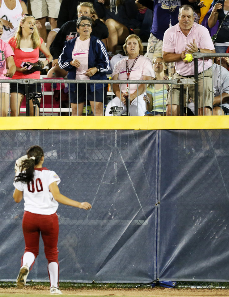 Photo - OU's Destinee Martinez (00) watches a fan try to catch a three-run home run by Tennessee's Madison Shipman (44) as it leaves the field in the eleventh inning during Game 1 of the Women's College World Series NCAA softball championship series between Oklahoma and Tennessee at ASA Hall of Fame Stadium in Oklahoma City, Monday, June 3, 2013. OU won 5-3 in 12 innings. Photo by Nate Billings, The Oklahoman