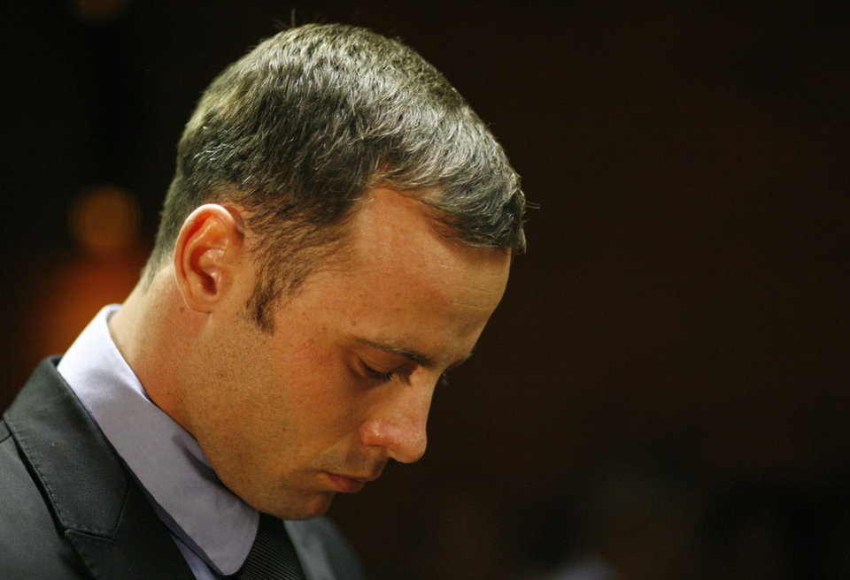 Olympic athlete Oscar Pistorius stands during his bail hearing at the magistrate court in Pretoria, South Africa, Thursday, Feb. 21, 2013. The lead investigator in the murder case against Pistorius faces attempted murder charges himself over a 2011 shooting, police said Thursday in another potentially damaging blow to the prosecution. Prosecutors said they were unaware of the charges against veteran detective Hilton Botha when they put him on the stand in court to explain why Pistorius should not be given bail in the Valentine\'s Day shooting death of his girlfriend. (AP Photo/Themba Hadebe)