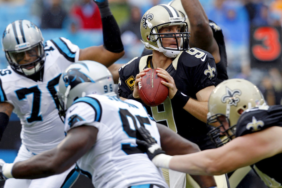 Photo -   New Orleans Saints quarterback Drew Brees (9) looks to pass under pressure from Carolina Panthers' Charles Johnson (95) and Greg Hardy (76) during the first quarter of an NFL football game in Charlotte, N.C., Sunday, Sept. 16, 2012. (AP Photo/Chuck Burton)