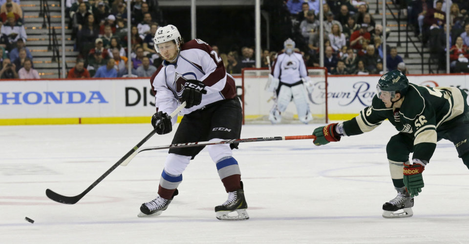 Photo - Colorado Avalanche center Nathan MacKinnon (29) passes to a teammate in front of Minnesota Wild left wing Erik Haula (56), of Finland, during the second period of Game 3 of an NHL hockey first-round playoff series in St. Paul, Minn., Monday, April 21, 2014. (AP Photo/Ann Heisenfelt)