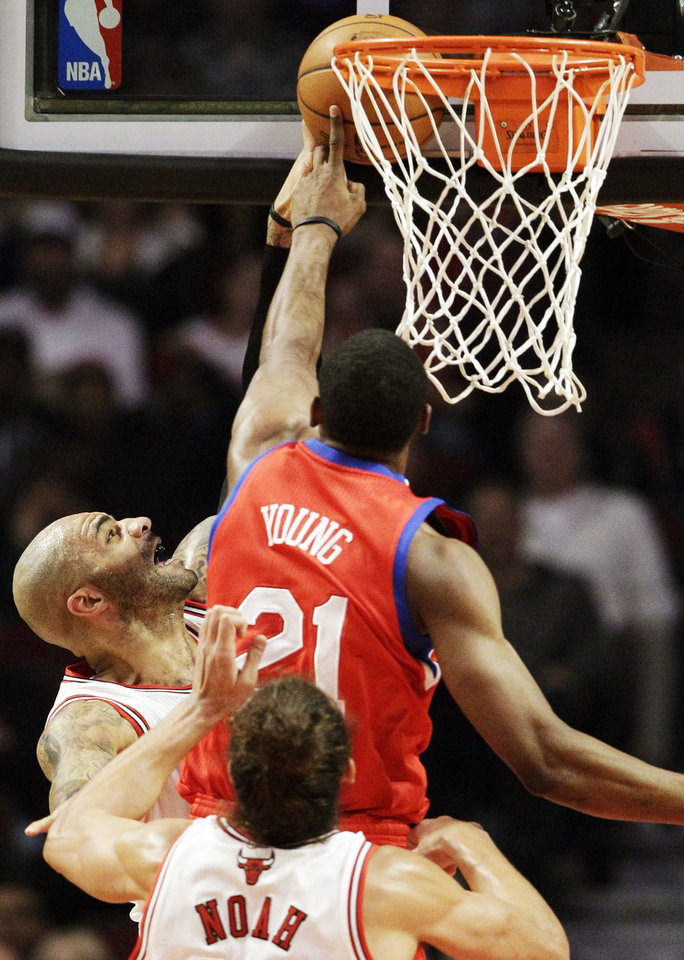 Philadelphia 76ers forward Thaddeus Young (21) blocks a shot by Chicago Bulls forward Carlos Boozer, left, as center Joakim Noah looks on during the first half of an NBA basketball game in Chicago on Saturday, Dec. 1, 2012. (AP Photo/Nam Y. Huh)