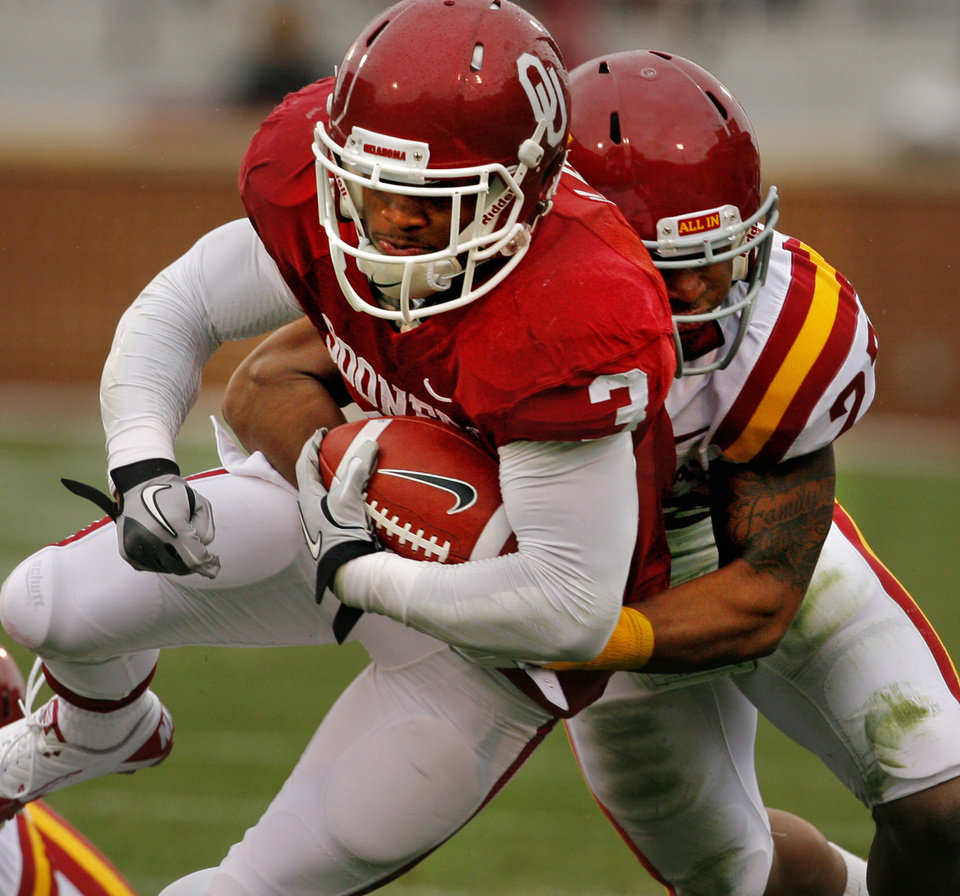 Photo - Oklahoma's Brennan Clay (3) is tackled by Iowa State's Leonard Johnson (23)during a college football game between the University of Oklahoma Sooners (OU) and the Iowa State University Cyclones (ISU) at Gaylord Family-Oklahoma Memorial Stadium in Norman, Okla., Saturday, Nov. 26, 2011. Photo by Steve Sinsey, The Oklahoman
