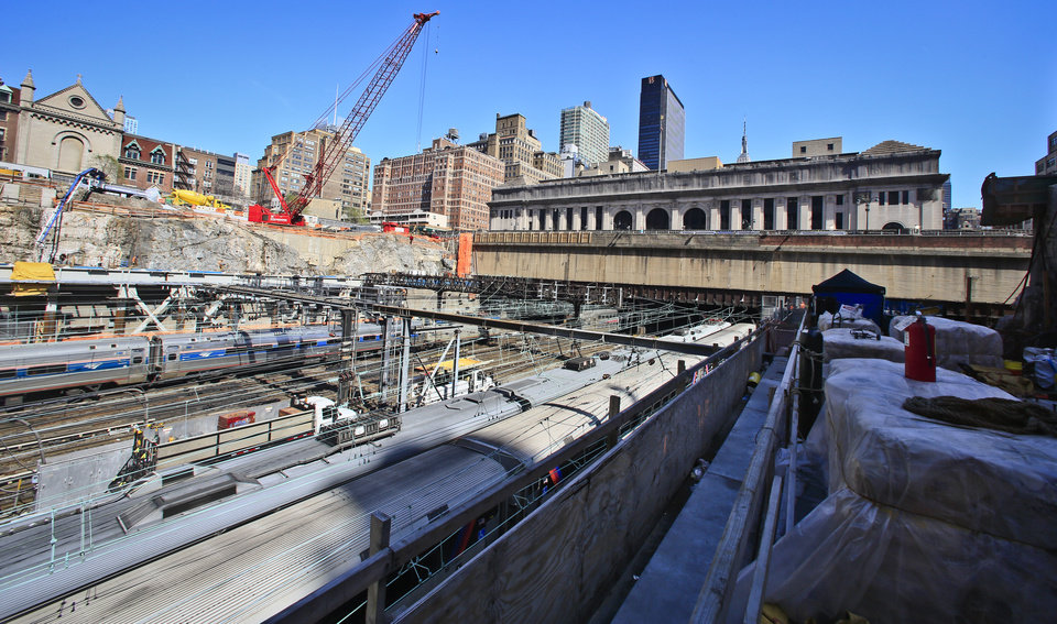 Photo - This photo shows commuter trains using tracks for Penn Station during ongoing construction of the Brookfield Manhattan West project, Wednesday April 16, 2014 in New York.  A $300 million concrete platform foundation is being constructed to completely cover the tracks for a $5 billion mixed-use complex between Tenth and Ninth avenues. (AP Photo/Bebeto Matthews)