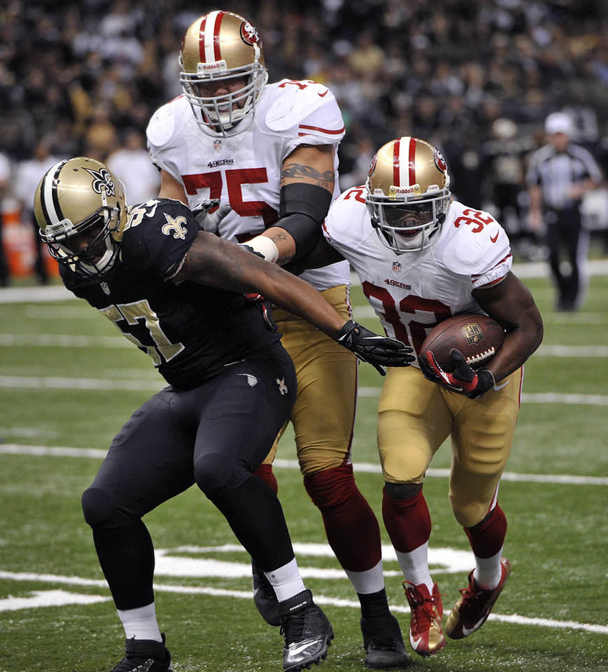 San Francisco 49ers running back Kendall Hunter (32) rushes past New Orleans Saints outside linebacker David Hawthorne (57) as San Francisco 49ers guard Alex Boone (75) blocks in the second half of an NFL football game at the Louisiana Superdome in New Orleans, Sunday, Nov. 25, 2012. (AP Photo/Bill Feig)