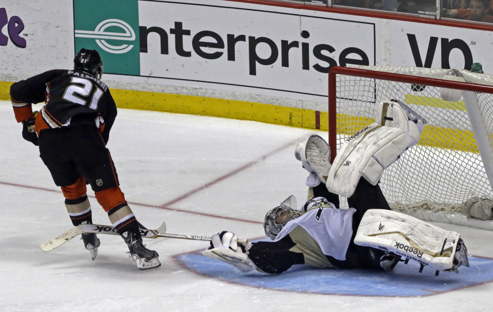 Photo - Pittsburgh Penguins goalie Marc-Andre Fleury (29) goes sprawling to block a shot by Anaheim Ducks right winger Kyle Palmieri (21) in a shootout in an NHL hockey game in Anaheim, Calif., Friday, March 7, 2014.  The Penguins won the shootout, 3-2. (AP Photo/Reed Saxon)