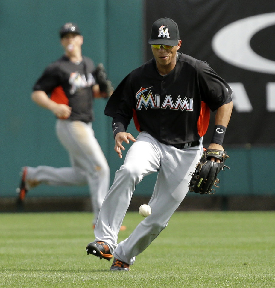 Photo - Miami Marlins center fielder Gorkys Hernandez chases down a single hit by Atlanta Braves' Justin Upton during the fifth inning of an exhibition spring training baseball game Monday, Feb. 25, 2013, in Kissimmee, Fla. (AP Photo/David J. Phillip)