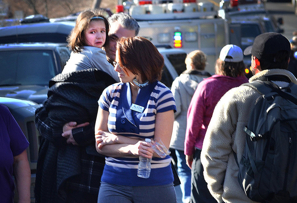 Photo - A young girl is comforted following a shooting at the Sandy Hook Elementary School in Newtown, Conn., about 60 miles (96 kilometers) northeast of New York City, Friday, Dec. 14, 2012. A gunman entered the school Friday morning and killed at least 26 people, including 20 young children. (AP Photo/The New Haven Register, Melanie Stengel)  ORG XMIT: CTNHR106