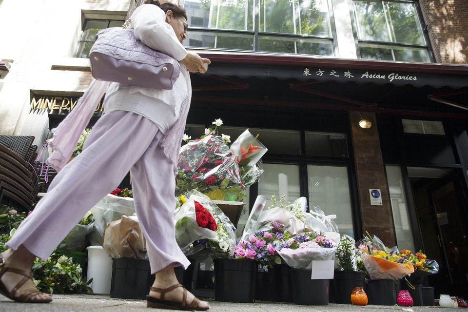Photo - A woman passes flowers placed in front of restaurant Asian Glories in Rotterdam, Saturday, July 19, 2014. Both owners, Jenny Loh and Popo Fan, were among those killed when a Malaysian jetliner was shot down over Ukraine Thursday. All passengers, 298 people from nearly a dozen nations, more than half being Dutch were killed. Malaysia Airlines said Saturday it has no immediate plans to fly the relatives of the 298 passengers and crew killed in the downing to visit the site in Ukraine because of security concerns. (AP Photo/Phil Nijhuis)