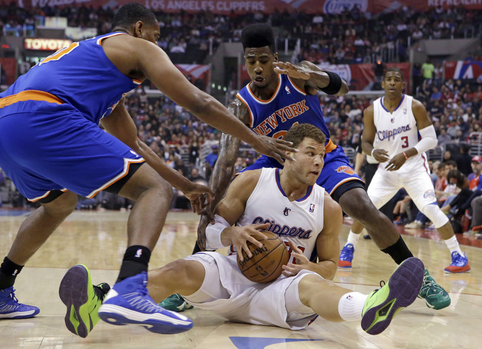 Los Angeles Clippers forward Blake Griffin (32) comes up with the ball in a floor scrum with New York Knicks forward Kurt Thomas, left, and  forward Iman Shumpert (21) in the first half of an NBA basketball game in Los Angeles Sunday, March 17, 2013. (AP Photo/Reed Saxon)
