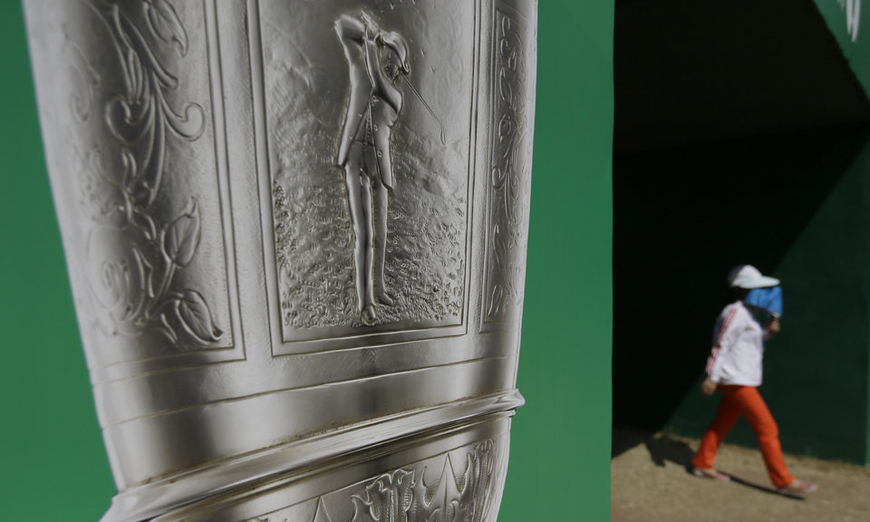 A golf fan walks onto the 10th hole passing an image of the Claret Jug trophy during the third round of the British Open Golf Championship at Muirfield, Scotland, Saturday July 20, 2013. (AP Photo/Jon Super)