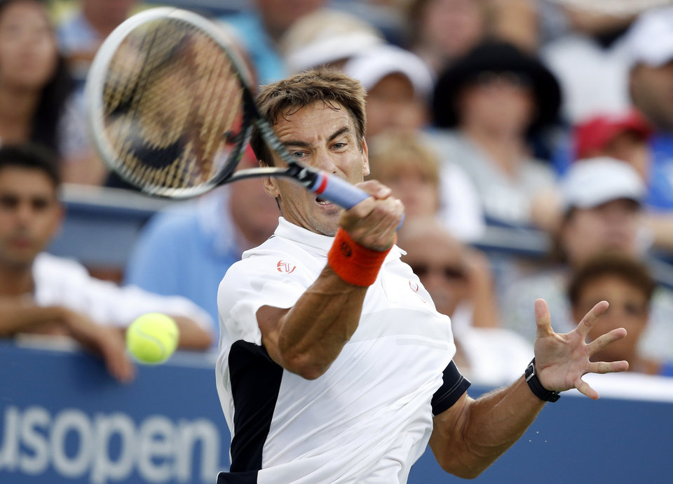 Photo - Tommy Robredo, of Spain, returns a shot to Stan Wawrinka, of Switzerland, during the fourth round of the U.S. Open tennis tournament Monday, Sept. 1, 2014, in New York. (AP Photo/Jason DeCrow)