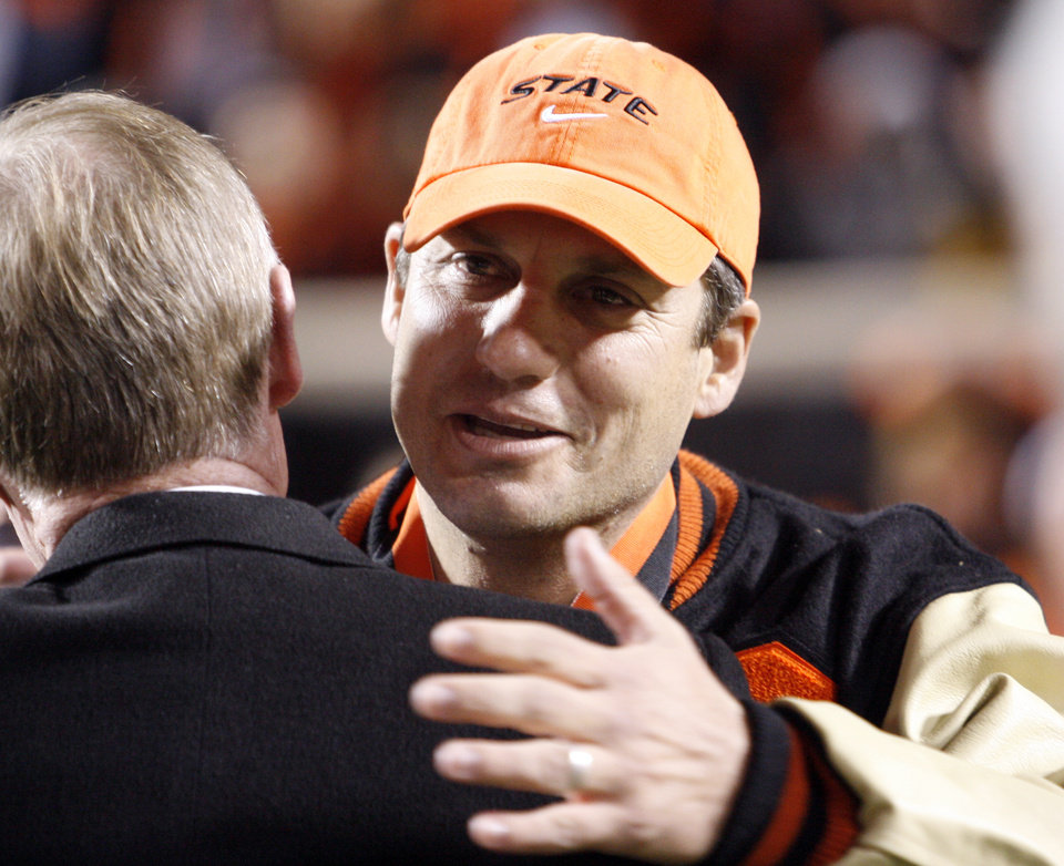 Photo - Robin Ventura hugs president Burns Hargis as he is inducted into the alumni hall of fame during the college football game between Oklahoma State University (OSU) and the University of Missouri (MU) at Boone Pickens Stadium in Stillwater, Okla. Saturday, Oct. 17, 2009.  Photo by Steve Sisney, The Oklahoman