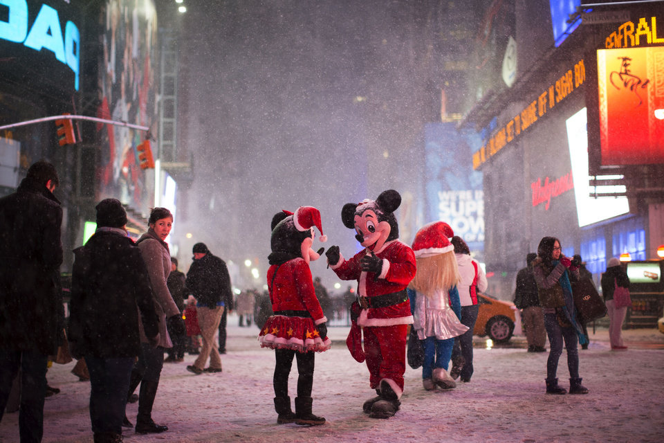 Photo - Two people dressed as Disney characters talk under falling snow in Times Square, Thursday, Jan. 2, 2014, in New York. The storm is expected to bring snow, stiff winds and punishing cold into the Northeast. (AP Photo/John Minchillo)