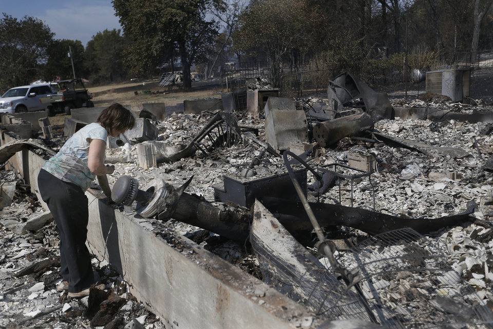 Marie Montelongo looks through her burned home, Sunday, Aug. 5, 2012, in Glencoe, Okla., after wildfires moved through the area Saturday. Photo by Sarah Phipps, The Oklahoman