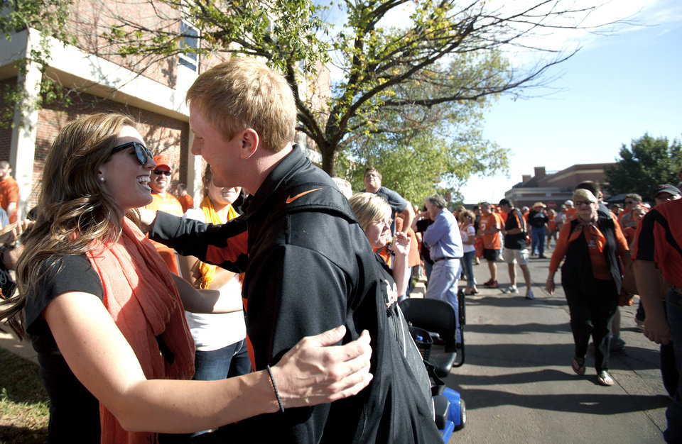 Photo - Melanie Weeden is greeted by Oklahoma State's Brandon Weeden (3 )during the spirit walk before the college football game between the Oklahoma State University Cowboys (OSU) and the University of Arizona Wildcats at Boone Pickens Stadium in Stillwater, Okla., Thursday, Sept. 8, 2011. Photo by Sarah Phipps, The Oklahoman  ORG XMIT: KOD