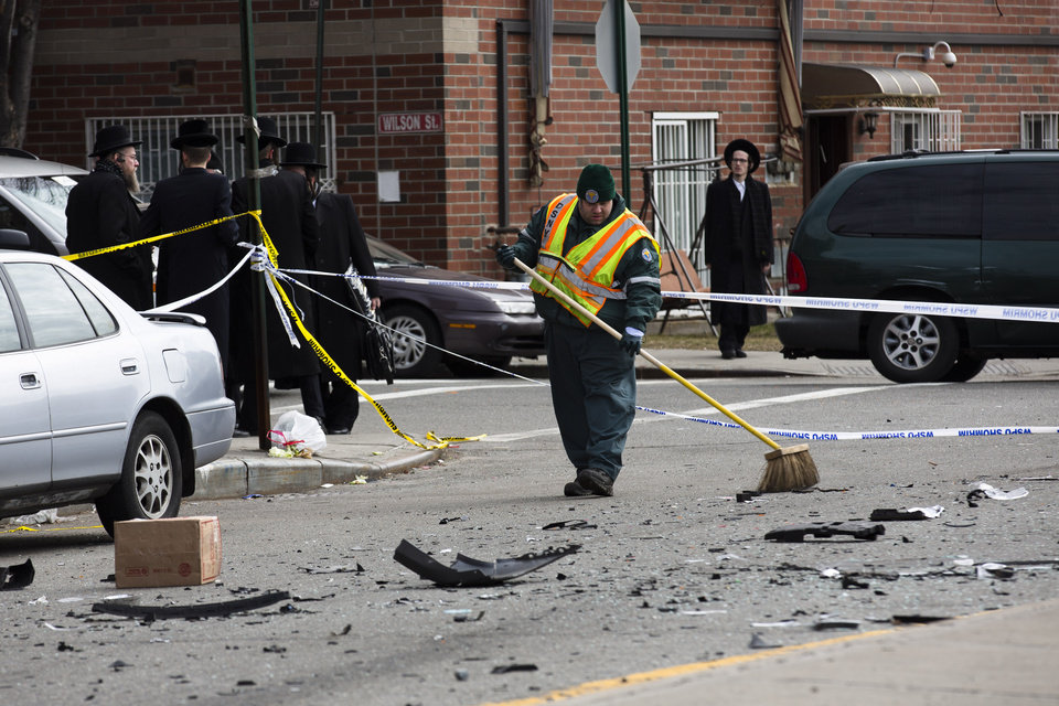 Photo - A worker clears debris  from a fatal accident that claimed the lives of two expectant parents, Sunday, March 3, 2013, in the Brooklyn borough of New York. A driver struck the car the couple were riding in early Sunday morning, killing both parents while their baby, who was born prematurely, survived and is in critical condition. (AP Photo/John Minchillo)